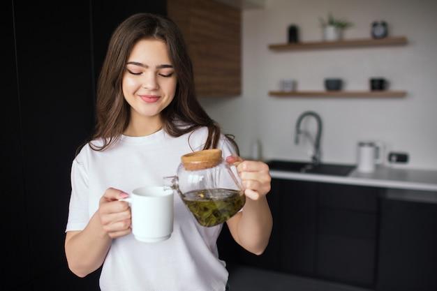 Jonge vrouw in de keuken tijdens de quarantaine. meisje in casual look en wit overhemd gieten wat thee uit theepot in witte kop. ik ga het drinken.