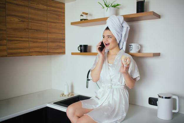 Jonge vrouw in de keuken tijdens de quarantaine. meisje na douche zitten en praten over de telefoon. houd smakelijke donut in de hand. online gesprek.
