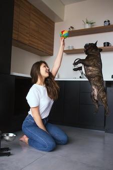 Jonge vrouw in de keuken tijdens de quarantaine. mooi meisje speelt met haar franse bulldog. de vrouw houdt stuk speelgoed in hand terwijl het puppy omhoog springt om het te krijgen.