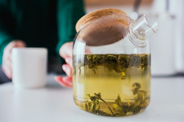 Jonge vrouw in de keuken tijdens de quarantaine. sluit omhoog en snijd mening van theepot met groene binnen thee. het meisje houdt het en witte kop in handen. onscherpe achtergrond.