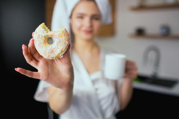 Jonge vrouw in de keuken tijdens de quarantaine. vaag beeld van meisje na het baden in witte handdoek en robe die stuk van doughnut in hand houden. kopje drinken in een andere.