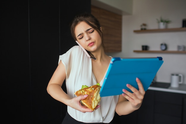 Jonge vrouw in de keuken zakenvrouw praten over de telefoon. houd grote tablet en sandwich in handen. thuiskantoor en werken op afstand. lunchperiode.