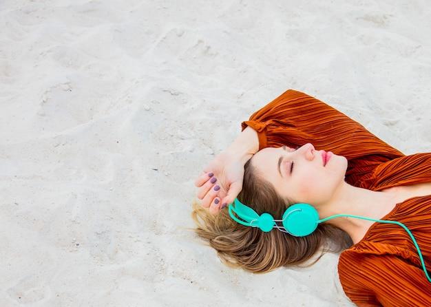 Jonge vrouw in de kleurenblouse van bourgondië met hoofdtelefoons het liggen