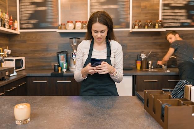 Jonge vrouw in de koffiewinkelarbeider van de schort bij bar counte