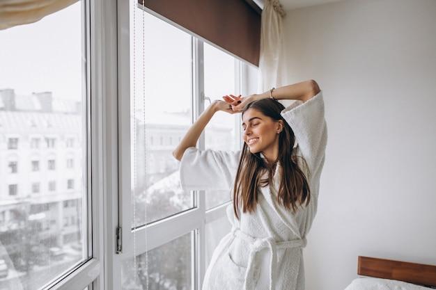Jonge vrouw in de ochtend die zich uitstrekt door het raam