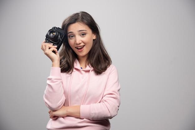 Jonge vrouw in de roze camera van de sweatshirtholding.