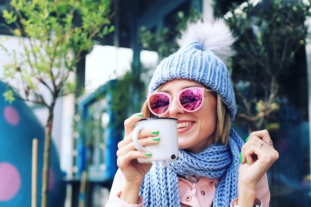 Jonge vrouw in de winter met gebreide muts en sjaal