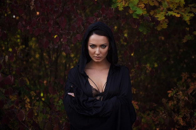 Jonge vrouw in de zwarte mantel in het de herfstbos