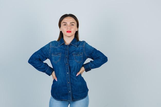 Jonge vrouw in denim overhemd en spijkerbroek hand in hand op de heup en er aantrekkelijk uitzien