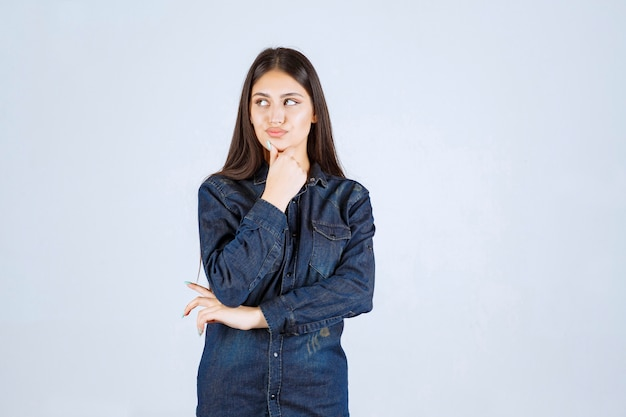 Jonge vrouw in denim overhemd neutrale en verleidelijke poses geven zonder reacties