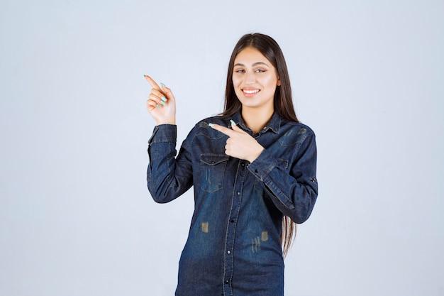 Jonge vrouw in denimoverhemd dat haar handen opheft en hierboven op iets richt