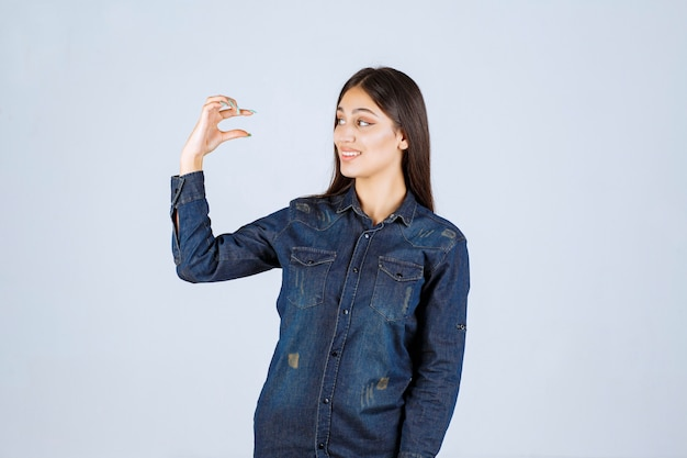 Jonge vrouw in denimoverhemd die de maatregelen van een voorwerp tonen