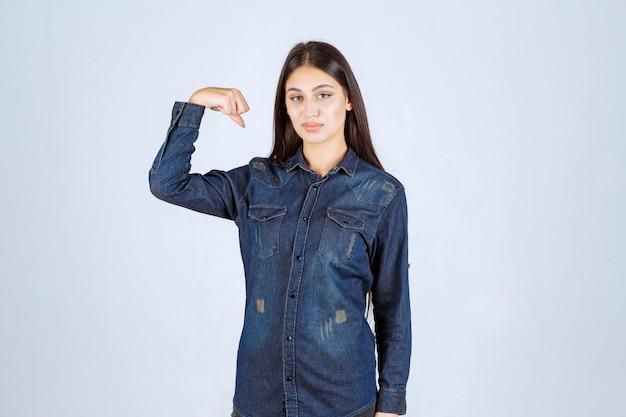 Jonge vrouw in denimoverhemd die haar wapenspieren tonen