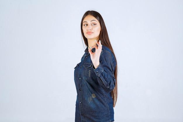 Jonge vrouw in denimoverhemd die plezierteken tonen