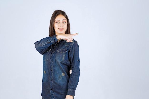 Jonge vrouw in denimoverhemd wijzend naar de rechterkant