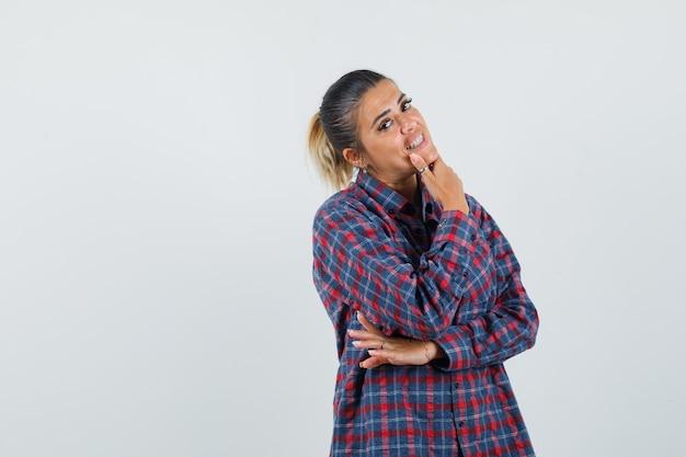 Jonge vrouw in denken pose terwijl wijsvinger op kin in geruit overhemd zetten en peinzende, vooraanzicht kijken.