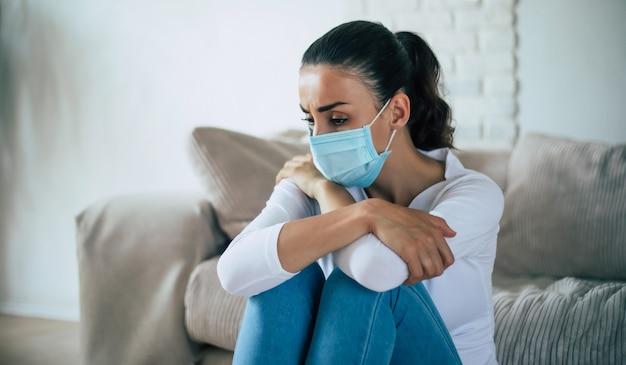Jonge vrouw in diepe depressie zit op de bank met een medisch veiligheidsmasker tijdens de quarantaine van het coronavirus