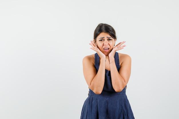 Jonge vrouw in donkerblauwe jurk die gezicht met handen aanraakt en er verontrust uitziet