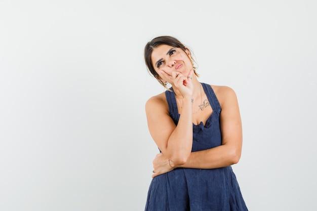 Jonge vrouw in donkerblauwe jurk die in denkende pose staat terwijl ze omhoog kijkt