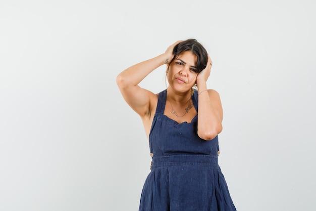 Jonge vrouw in donkerblauwe jurk poseren met de handen op het hoofd en ziet er verrukkelijk uit