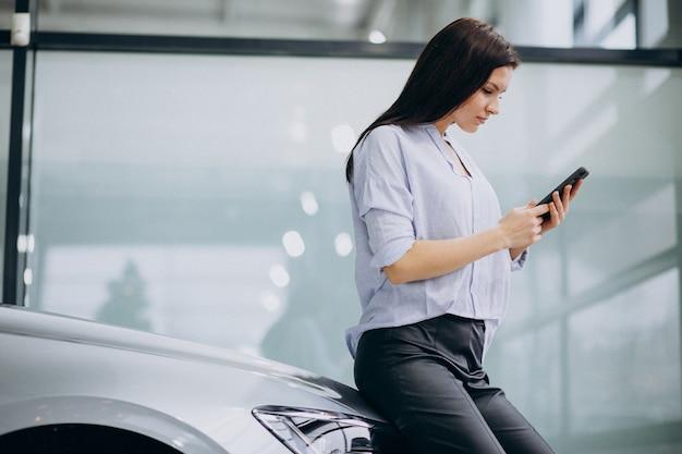 Jonge vrouw in een autoshowruimte die telefoon met behulp van