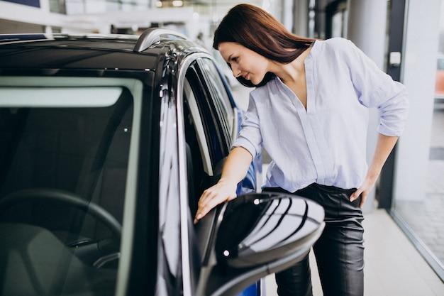Jonge vrouw in een autotoonzaal die een auto kiest