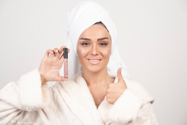 Jonge vrouw in een badjas die een lippenstift houdt en een duim toont