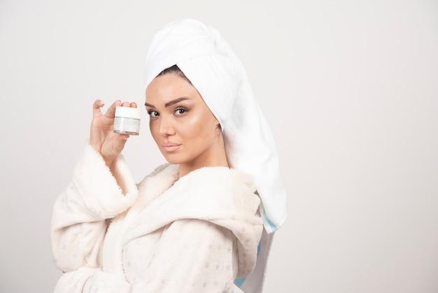Jonge vrouw in een badjas die een room houdt