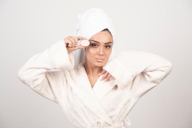 Jonge vrouw in een badjas die samenstelling doet