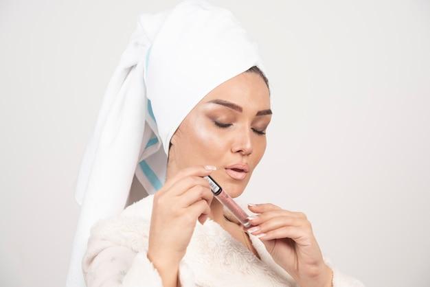 Jonge vrouw in een badjas met een lippenstift