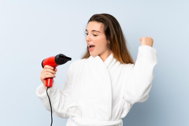 Jonge vrouw in een badjas met haar haardroger een overwinning vieren