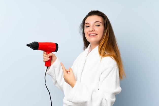 Jonge vrouw in een badjas met haardroger en wijst het