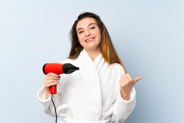 Jonge vrouw in een badjas met haardroger, wijzend naar de zijkant