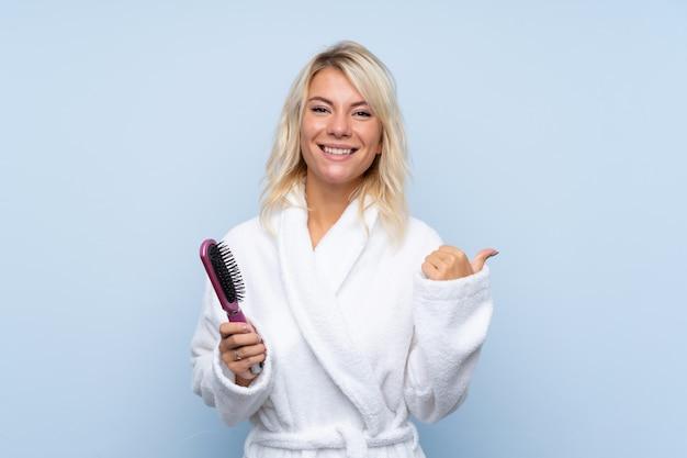 Jonge vrouw in een badjas met haarkam die aan de kant richt om een product te presenteren