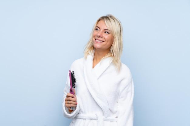 Jonge vrouw in een badjas met haarkam die omhoog terwijl het glimlachen kijkt