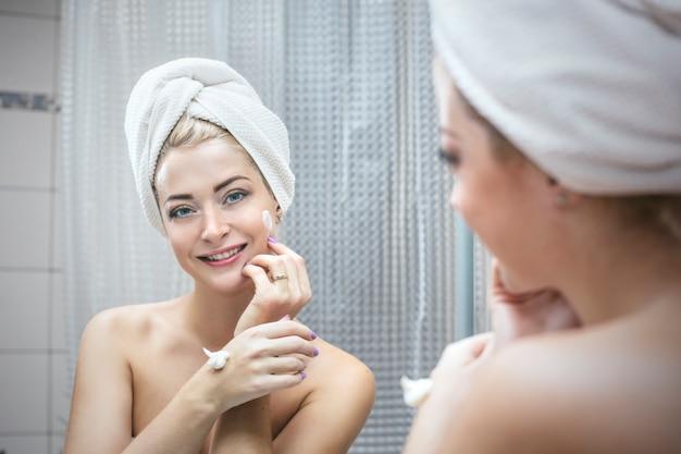Jonge vrouw in een badkamer heeft cosmetische ingrepen om schoonheid en gezondheid in een handdoek te verbeteren