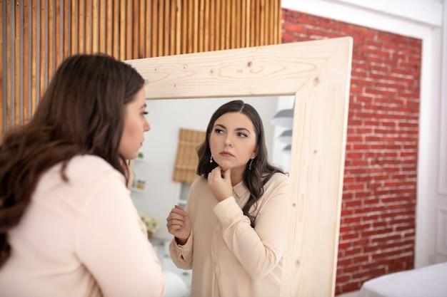 Jonge vrouw in een beige blouse die haar gezicht onderzoekt