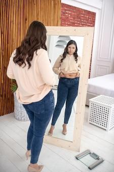Jonge vrouw in een beige blouse die naar zichzelf kijkt