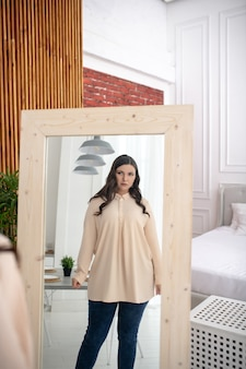 Jonge vrouw in een beige blouse die zichzelf in de spiegel bekijkt