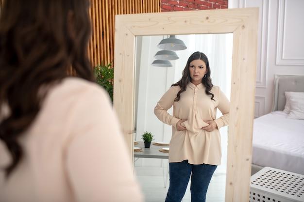 Jonge vrouw in een beige blouse wat betreft haar buik