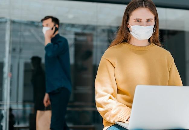 Jonge vrouw in een beschermend masker gebruikt haar laptop op straat
