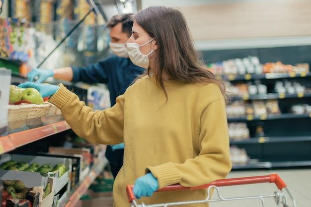Jonge vrouw in een beschermend masker koopt appels