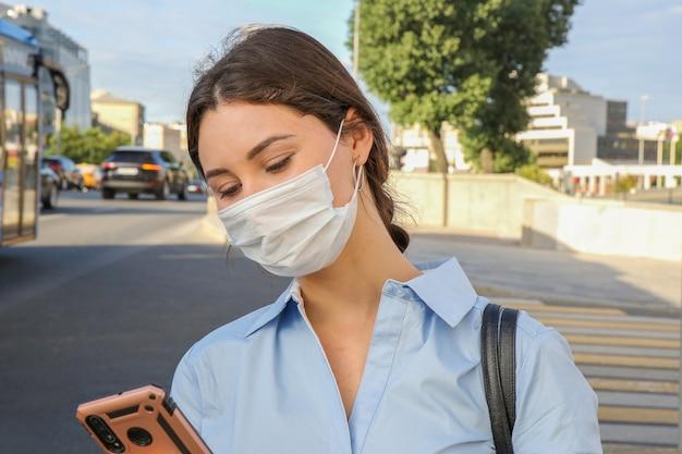 Jonge vrouw in een beschermend masker met een telefoon