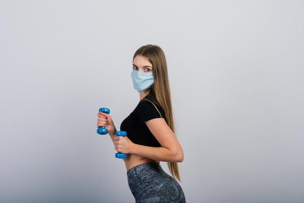 Jonge vrouw in een beschermend masker met halters. sporten in quarantaine, covid.