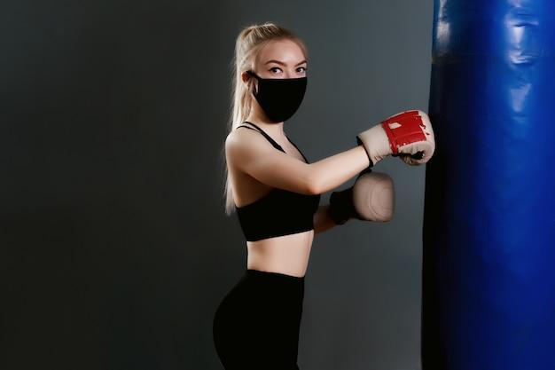 Jonge vrouw in een beschermend masker raakt een bokszak. beschermende maskers tegen virusinfectie. trainen tijdens quarantaine in de sportschool