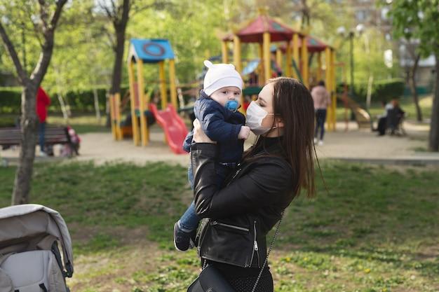 Jonge vrouw in een beschermend masker speelt met haar jonge zoon op straat