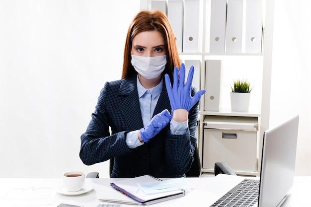 Jonge vrouw in een beschermend masker zet op beschermende handschoenen. zakenvrouw in een medisch masker op de werkplek.