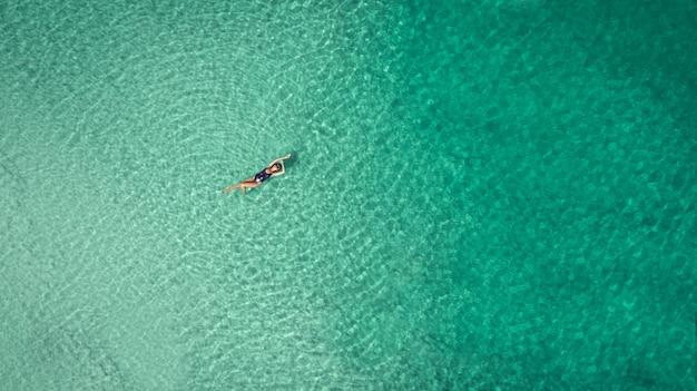 Jonge vrouw in een bikini die op de rug op het witte zand dichtbij de golven van blauwe overzees ligt
