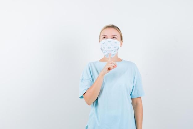 Jonge vrouw in een blauw t-shirt met een medisch masker