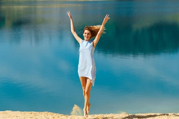 Jonge vrouw in een blauwe jurk die op het strand aan de oceaan springt. fijne vakantie